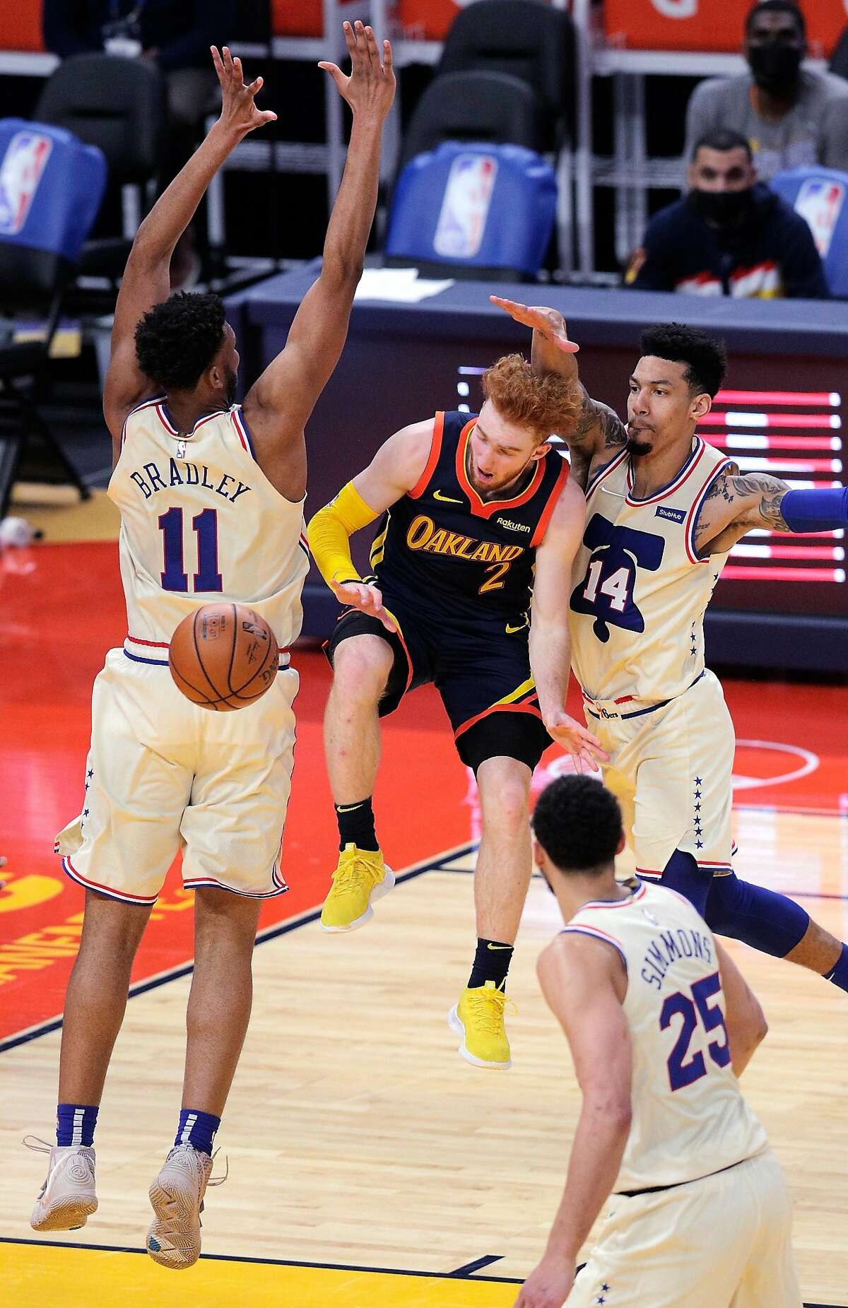 Golden State's Nico Mannion looks to pass while driving between Tony Bradley, left, and Danny Green of the Philadelphia 76ers at Chase Center on March 23.