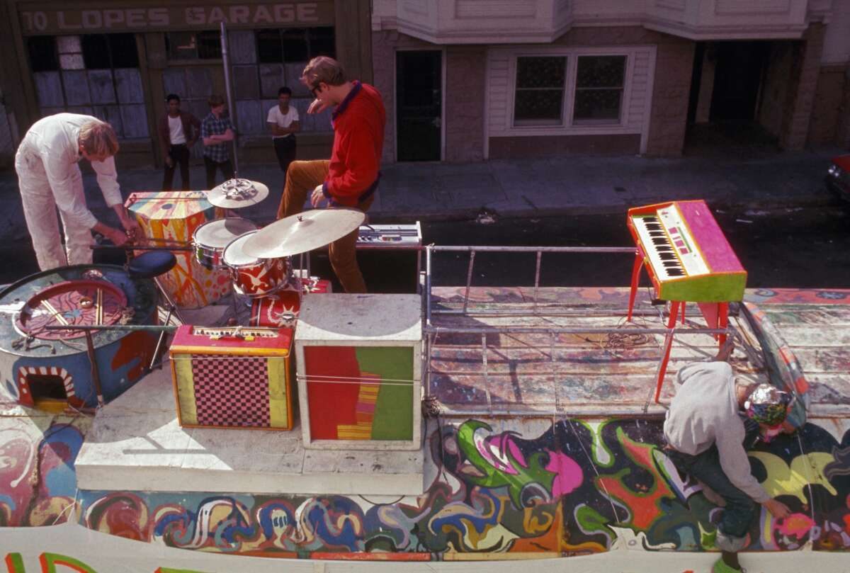 Stewart Brand and another member of the Merry Pranksters check the instruments on top of The Bus, while Anthony Dean Wells, known as the Hermit, paints The Bus with Day-Glo colors. They are preparing for the Acid Test Graduation in San Francisco, October 1966.