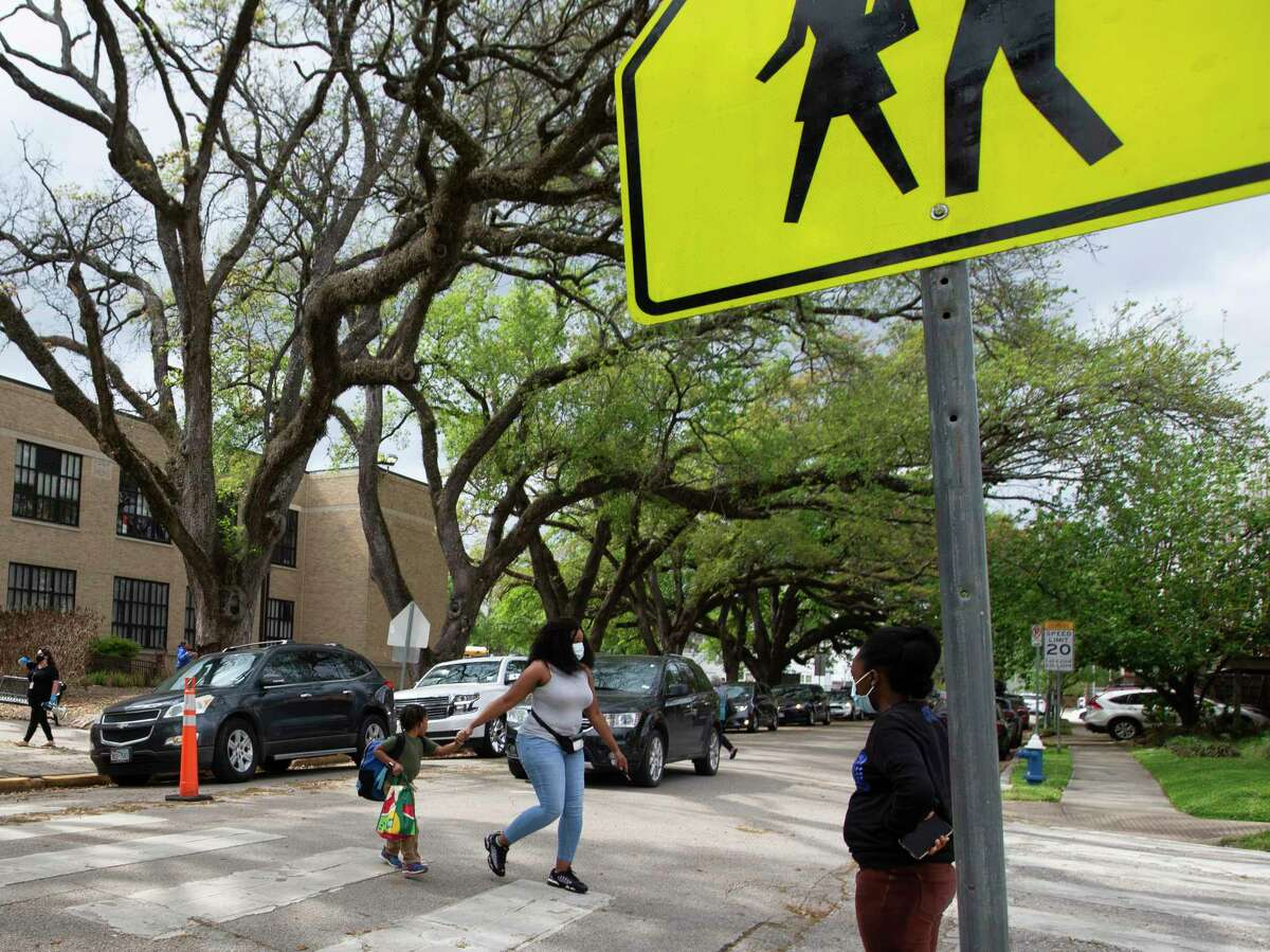Damita Roberts holding Dash roberts to cross an intersection after school Tuesday, March 30, 2021, at Woodrow Wilson Montessori School in Houston. Houston ISD trustees are expected to decide later this month whether former president Woodrow Wilson's racist beliefs and actions warrant removing his name from a Montrose-area campus, the latest flashpoint in a nationwide debate over symbolic remembrances of historical figures.