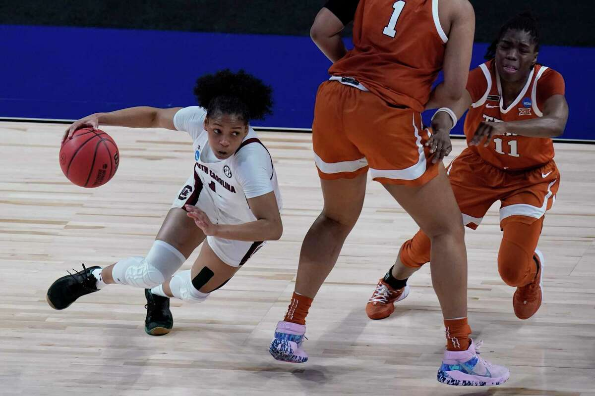 South Carolina guard Zia Cooke (1) drives around Texas forward Lauren Ebo (1) and guard Joanne Allen-Taylor (11) during the first half of a college basketball game in the Elite Eight round of the women's NCAA tournament at the Alamodome in San Antonio, Tuesday, March 30, 2021. (AP Photo/Eric Gay)