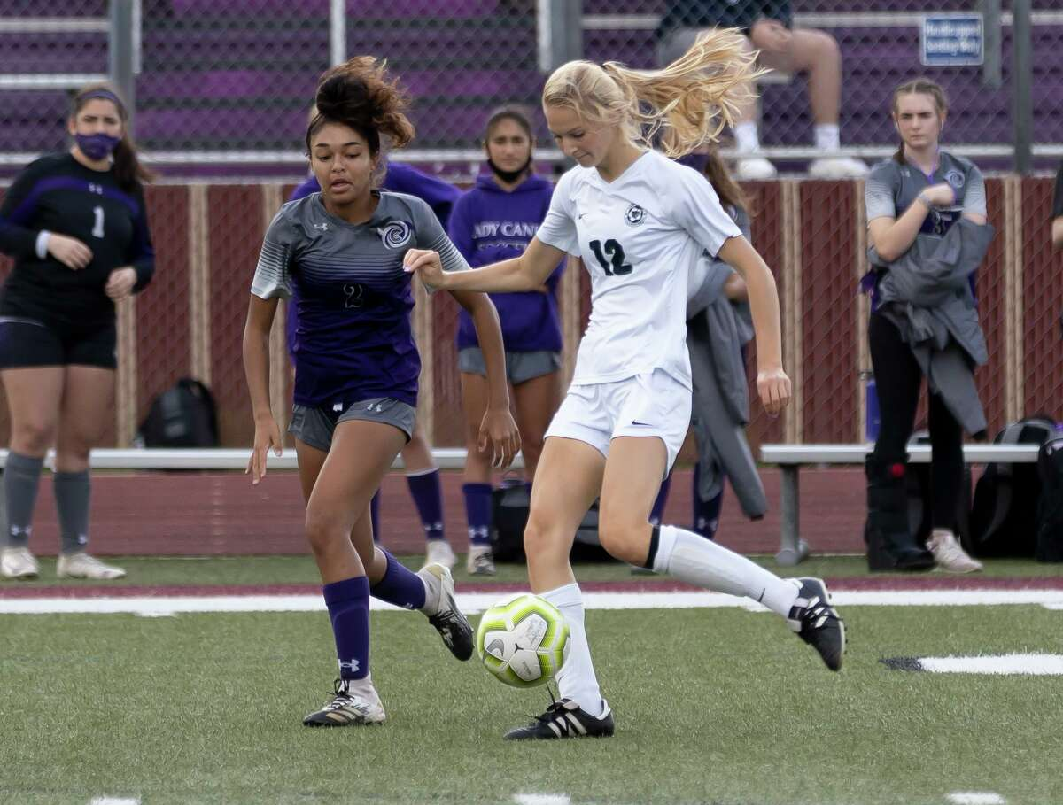College Park Carli Rabson (12) drives the ball while under pressure by Klein Cain midfielder Sydnee Smith (2) during the first half of a Region II-6A area playoff match at Magnolia West High School, Tuesday, March 30, 2021, in Magnolia.