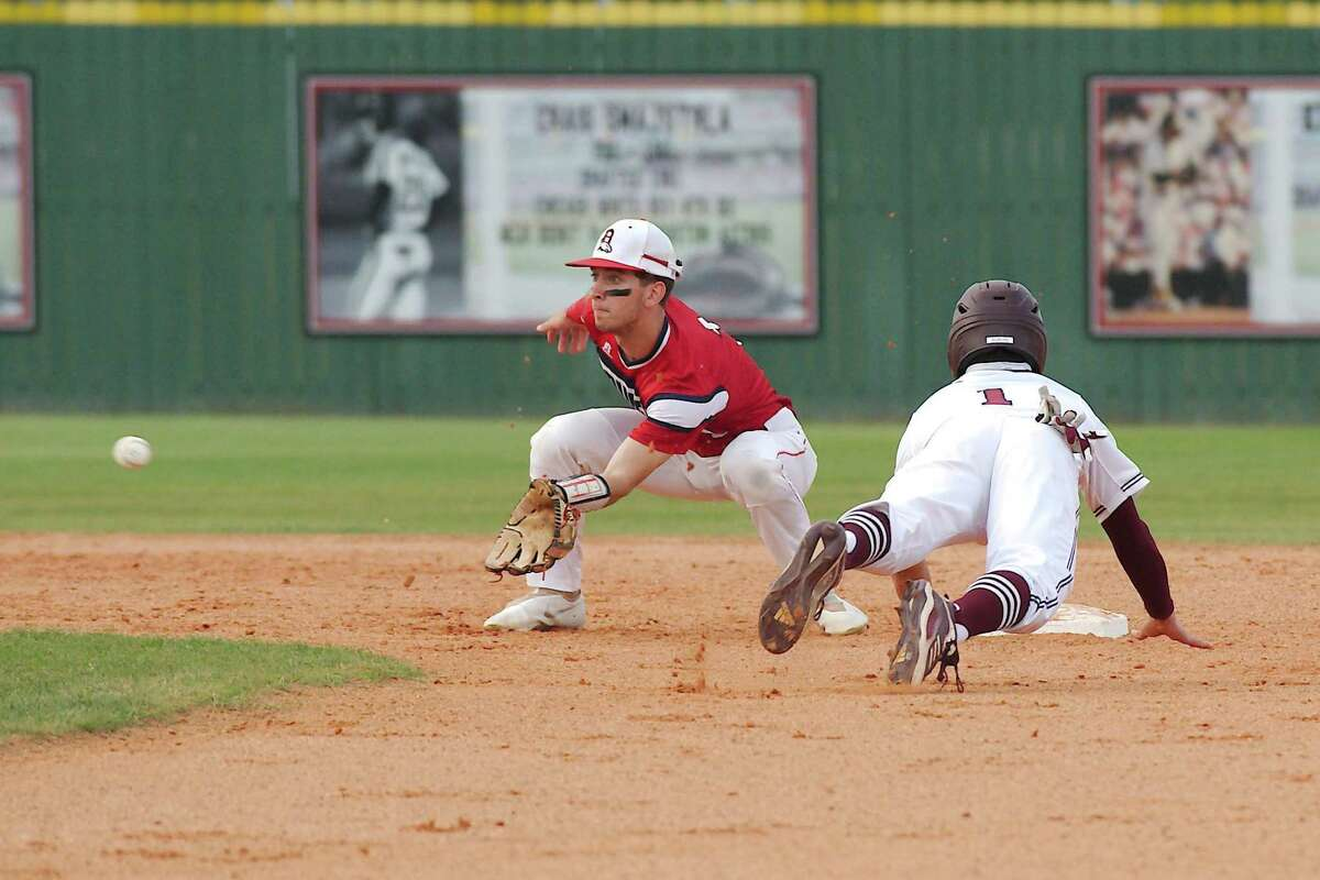Pearland's Anthony Avalos (1) dives to beat the throw to Dawson's Cole Sebok (1) Tuesday at Pearland High School.