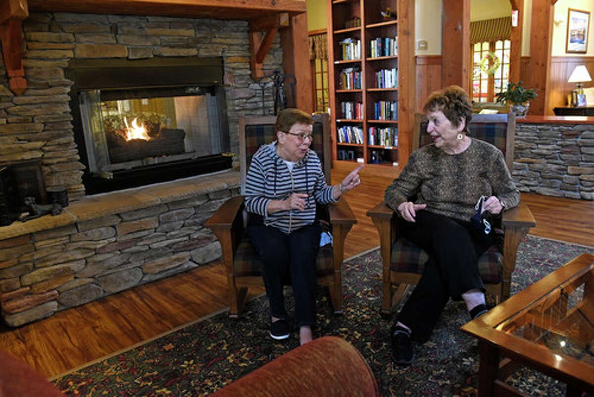 Avila residents Kathy DeLaMater, left, and Marilyn Seidenberg are seen chatting in front of the fireplace in the lobby at the Avila Retirement Community on Monday, March 29, 2021 in Albany, N.Y. (Lori Van Buren/Times Union)