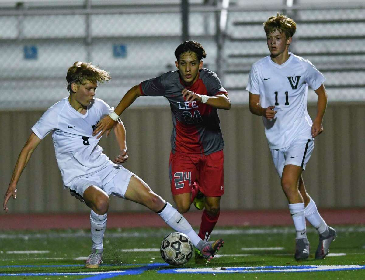 Julian Sanchez of LEE, middle, drives the ball enroute to a goal as Cade Dougan (5) and Thompson Schmeil (11) of Austin Vandegrift defend during Area Playoff action at Comalander Stadium on Tuesday, March 30, 2021.