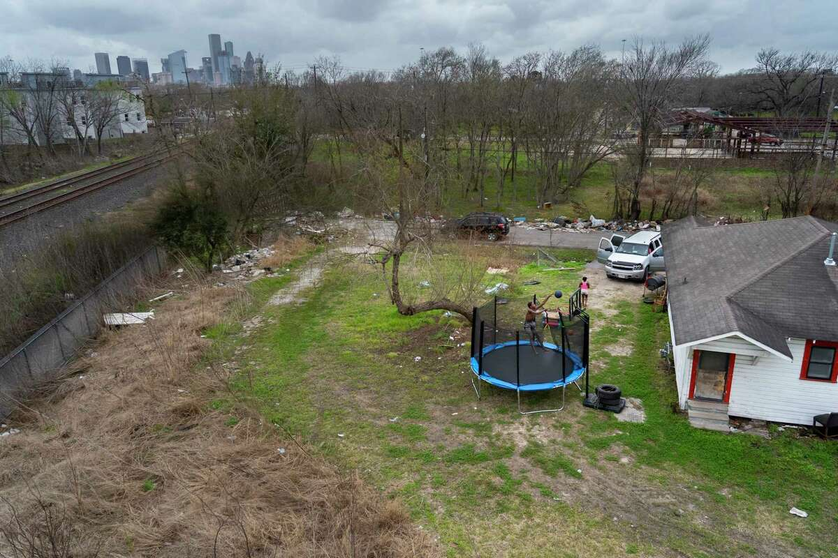 Kalvin Williams, 13, plays basketball on a trampoline behind his home in Fifth Ward on Wednesday, March 10, 2021, in Houston. Burst pipes along a row of four rental houses on the street have left Williams and his family without running water since the freeze in February.