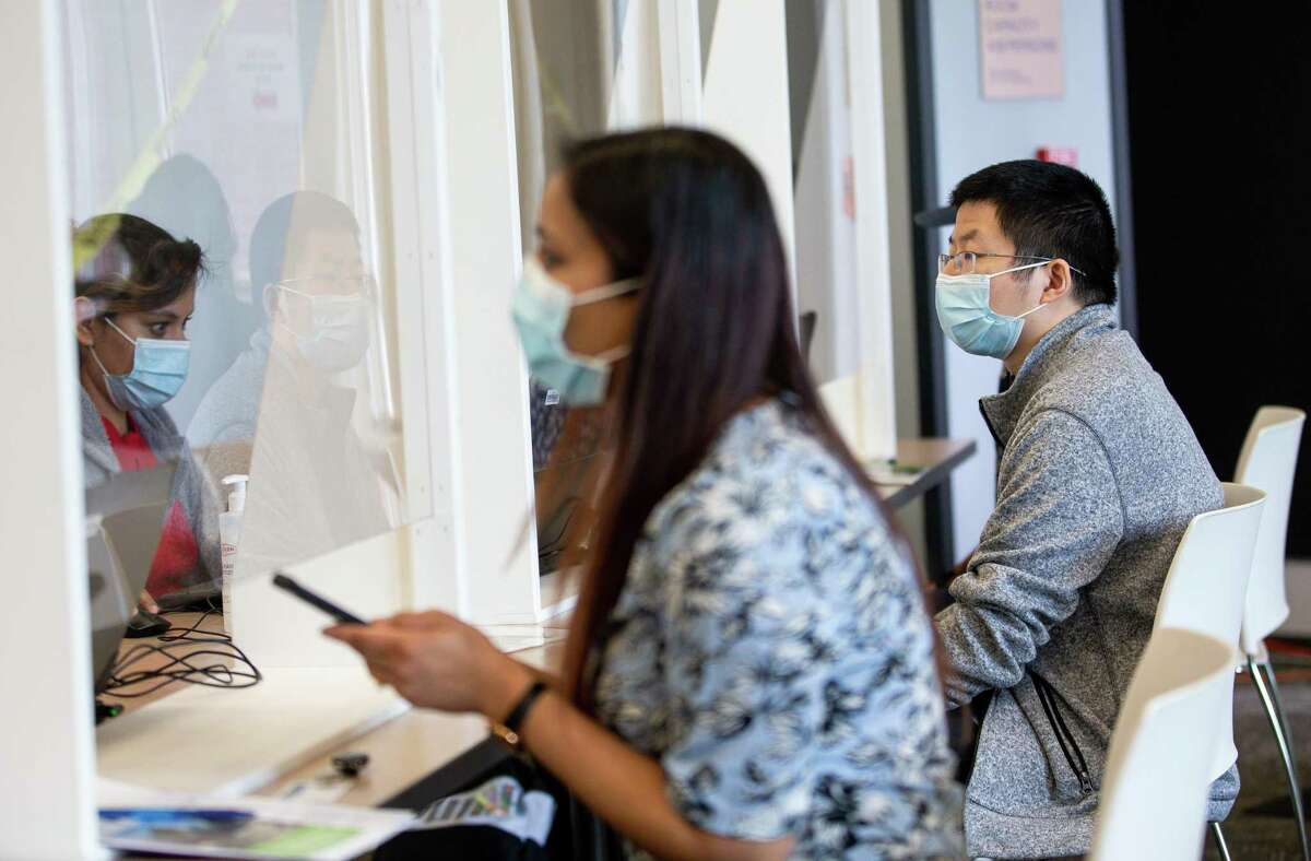 Chunruo Duan, right, and Pratibha Singh, foreground, go through the registration process to get the first dose of the Pfizer COVID-19 vaccine at Rice University's Bioscience Research Collaborative building on Monday, March 29, 2021, in Houston.