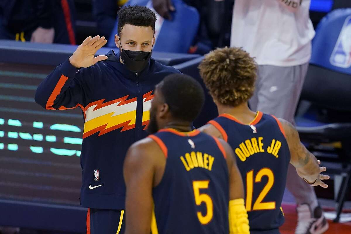 Golden State Warriors guard Stephen Curry, left, greets Kevon Looney (5) and Kelly Oubre Jr. (12) during the first half of the team's NBA basketball game against the Philadelphia 76ers in San Francisco, Tuesday, March 23, 2021. (AP Photo/Jeff Chiu)