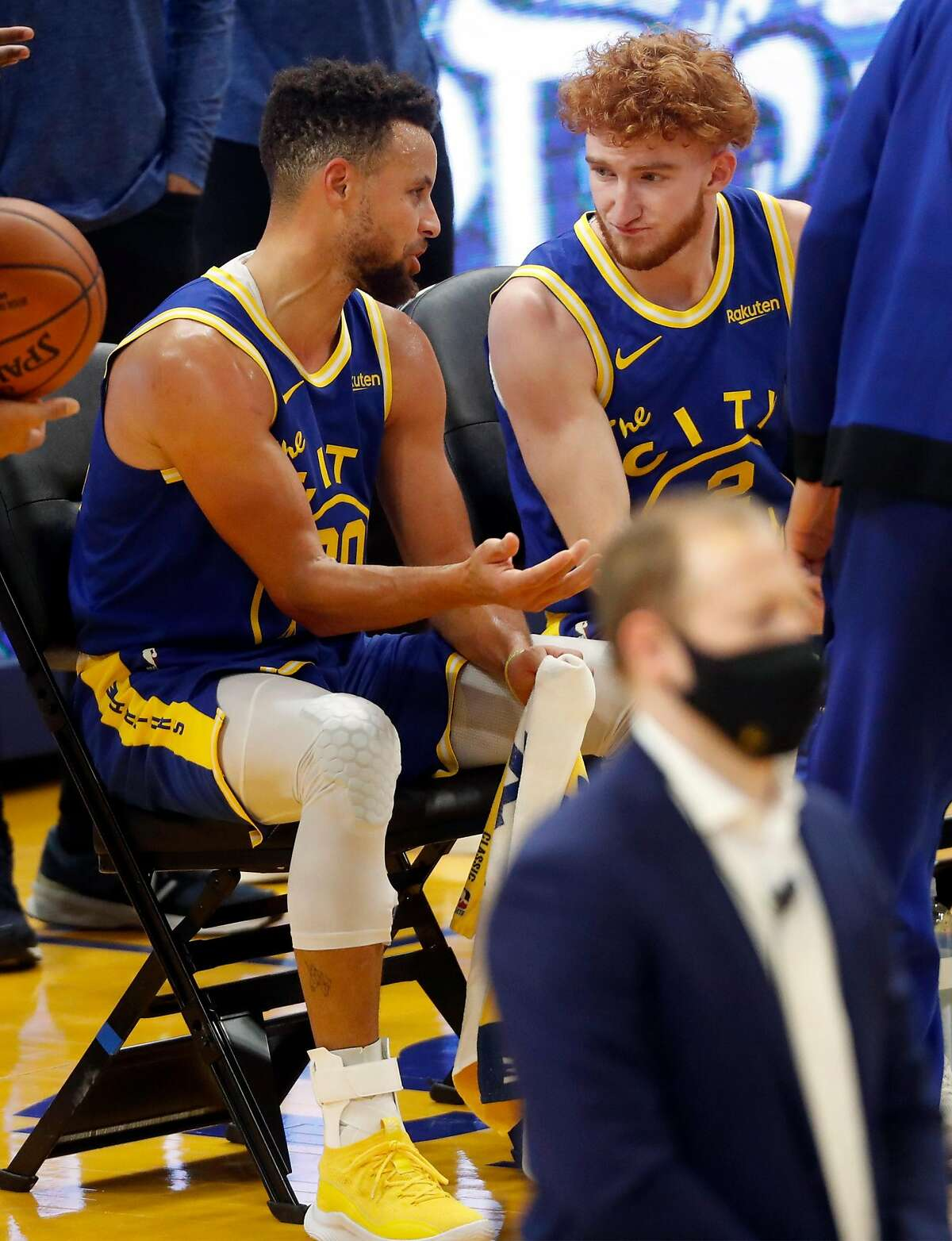 Stephen Curry talks with Warriors' backup point guard Nico Mannion during a timeout in a Jan. 21 game against New York at Chase Center.