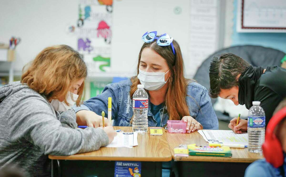 Kendalyn Weber (left) and Isaac Navan work with teacher Elizabeth Harlan at Deer Park Elementary School, where 99 percent of students have returned to campus, Tuesday, March 30, 2021, in Deer Park.