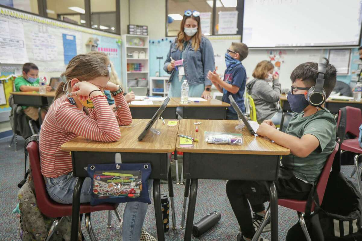 Third grader Kate Freeman (left) and Rogelio Martinez read books on a mobile device as they attended in person class at Deer Park Elementary School that has 99% of students in the classroom Tuesday, March 30, 2021, in Deer Park.