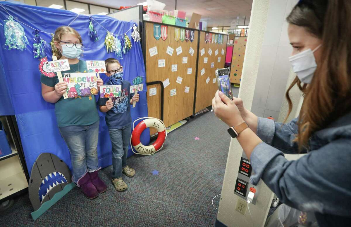Third graders Olivia Lucas and Aaron Brown have their photo taken by teacher Elizabeth Harlan at Deer Park Elementary School, where 99 percent of the student body has returned to campus, Tuesday, March 30, 2021, in Deer Park.