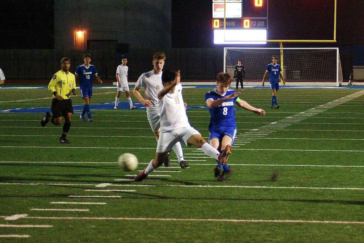 Friendswood's Louis Catchpole (8) kicks the ball past Santa Fe's Ian Montes (11) Tuesday, Mar. 16 at Friendswood High School.