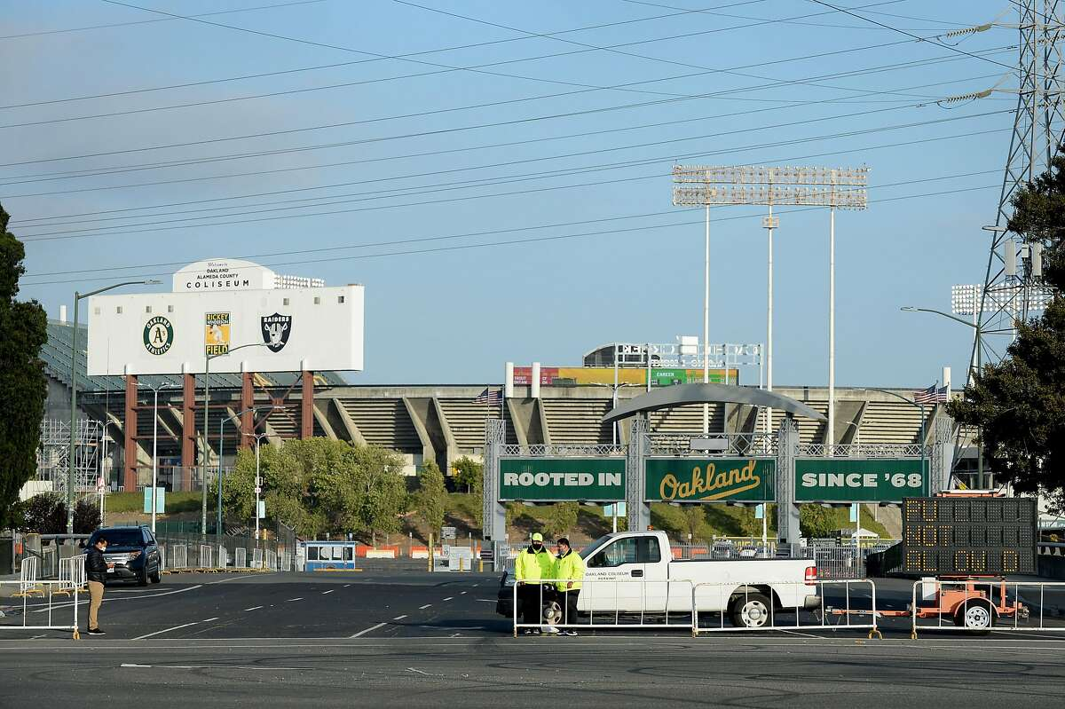 Event staff stands at the entrance of a vacant parking lot outside the Oakland Coliseum on July 24, 2020, during the Oakland A's home opener game against the L.A. Angels in Oakland, Calif.