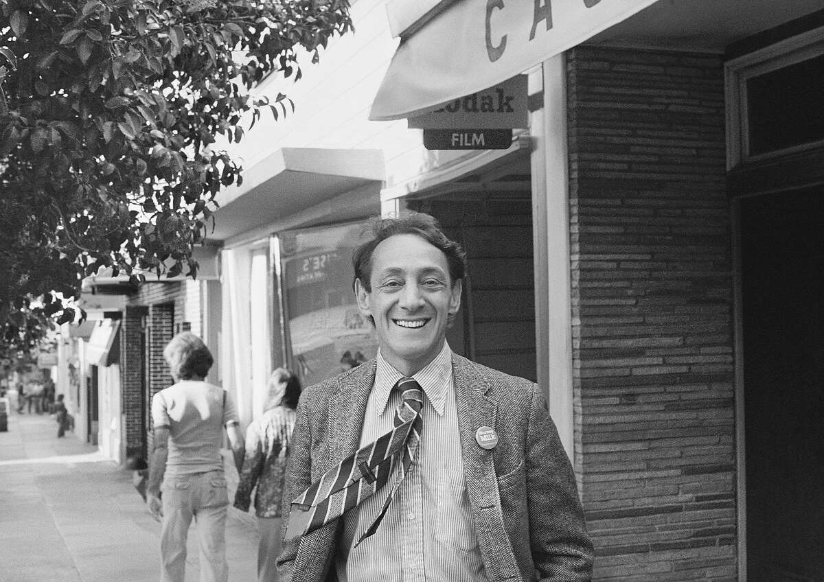 """Harvey Milk stands in front of his Castro Street Camera Store in 1977. On May 22, 2021, Gov. Gavin Newsom officially proclaimed the date to be """"Harvey Milk Day."""""""