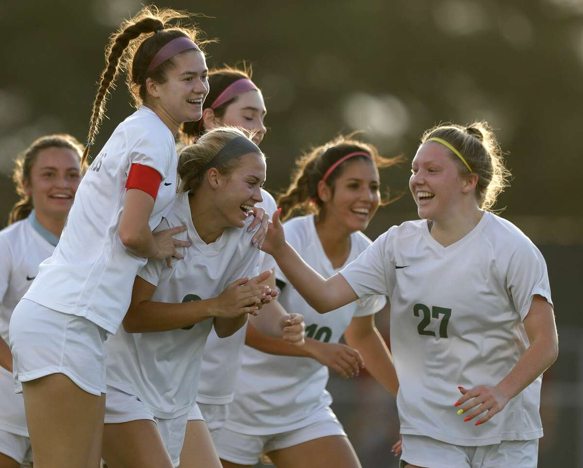 The Woodlands midfielder Emily Bates (9) celebrates after scoring a free-kick goal during the first period of a high school girls soccer playoff match at Klein Oak High School, Tuesday, March 30, 2021, in Spring.