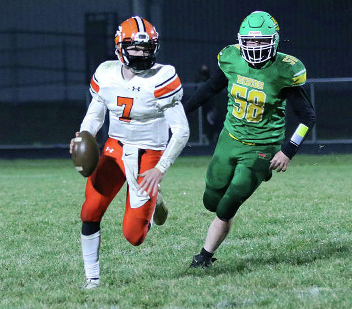 Gillespie quarterback Zach Reiniesch (7) looks for a receiver while Southwestern's Joe Reno gives chase in a SCC football game Friday night at Knapp Field in Piasa.