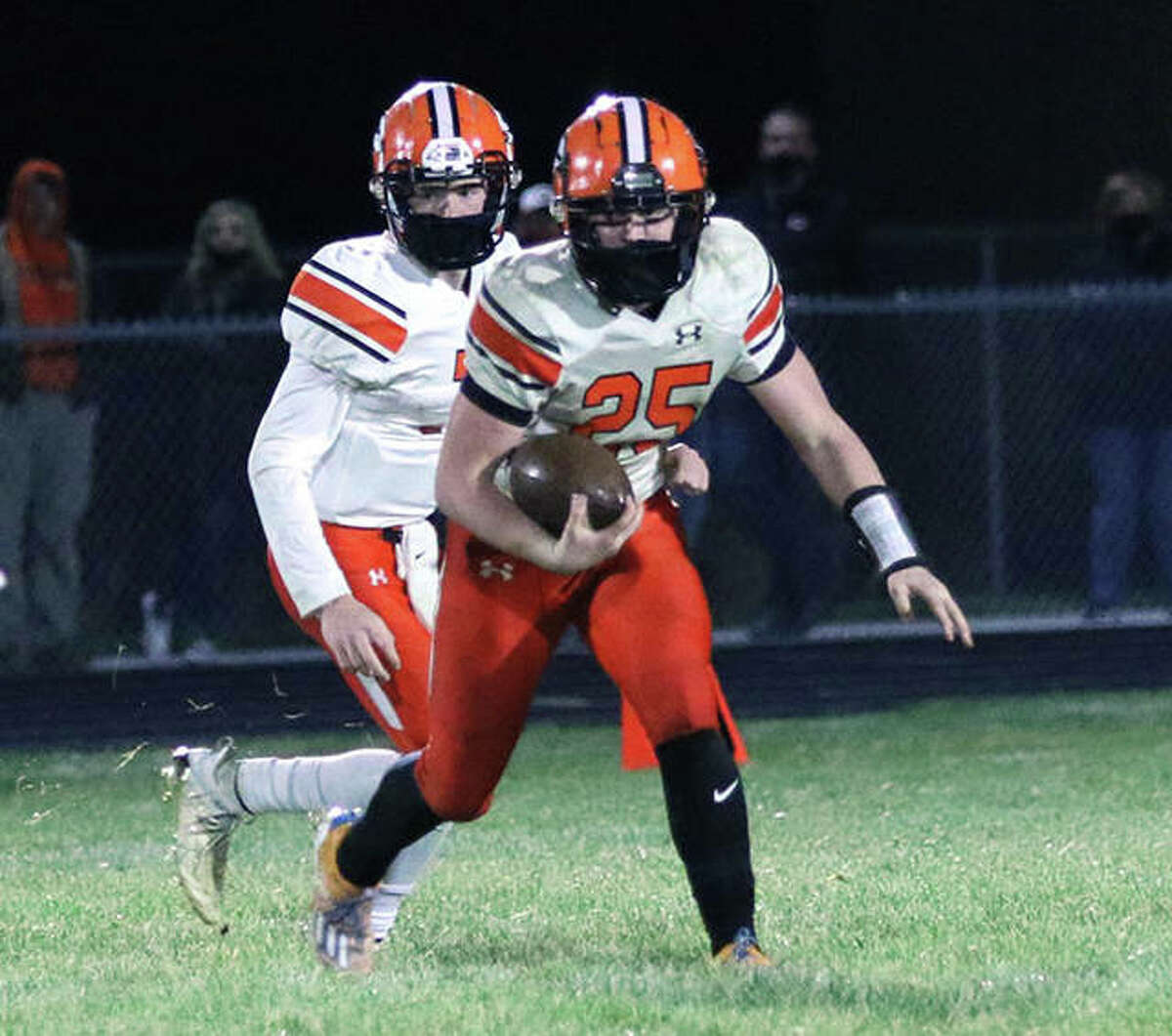 Gillespie's Dillon Lewis (25) looks for running room after taking the handoff from QB Zach Reiniesch in Friday's game against Southwestern in Piasa.