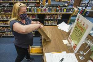 Library aide Mary Bourbina fills a paper bag with seeds pulled from the new seed library at the Grace A. Dow Memorial Library Wednesday afternoon, March 31, 2021 in Midland. (Katy Kildee/kkildee@mdn.net)