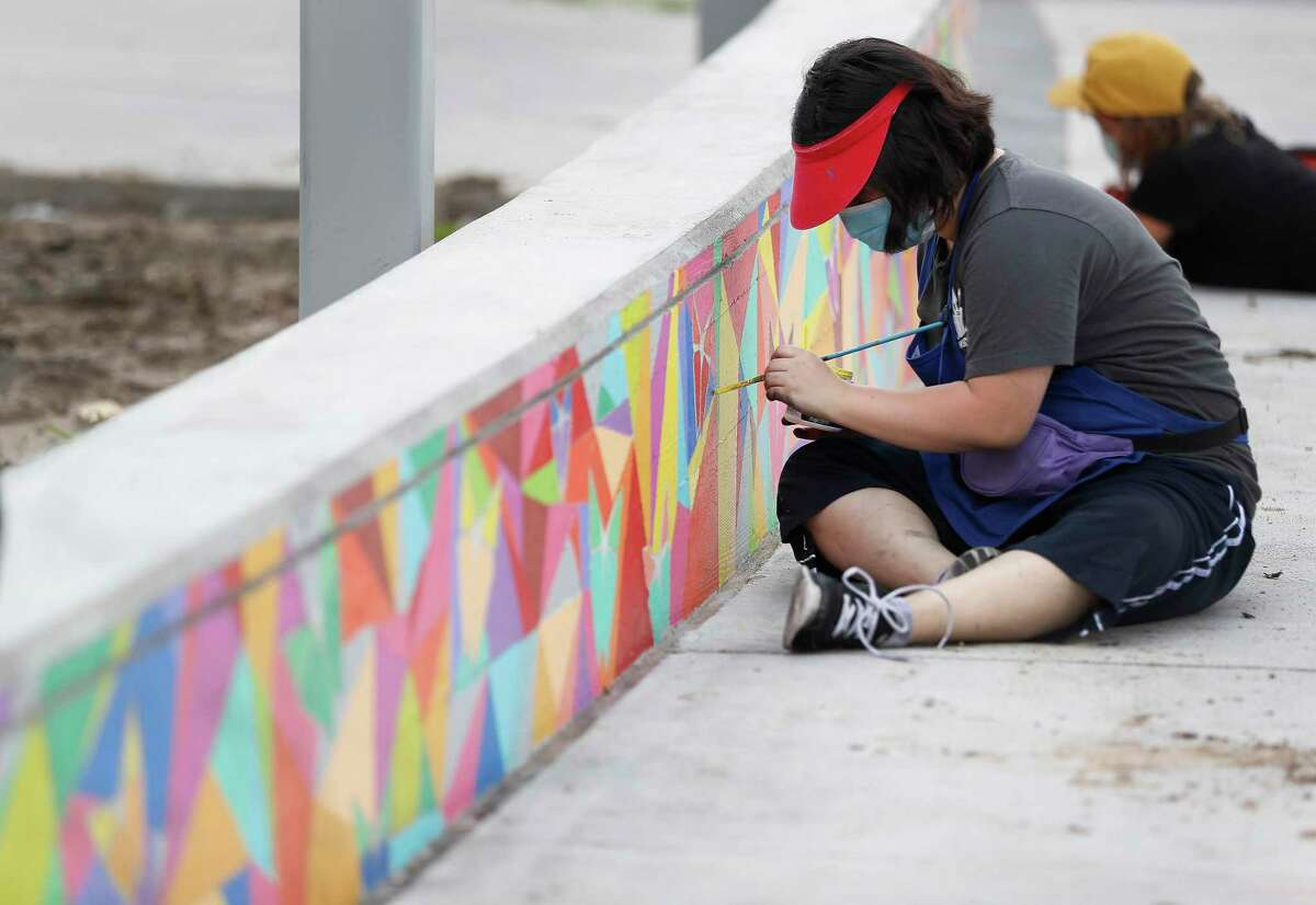 High school and college art students from the non-profit Newspring work on painting a colorful 90-foot mural outdoor seat mural.