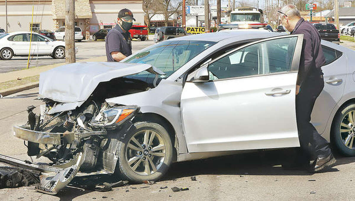 Wood River firefighters check over a Hyundai Elantra extensively damaged in an accident Wednesday.