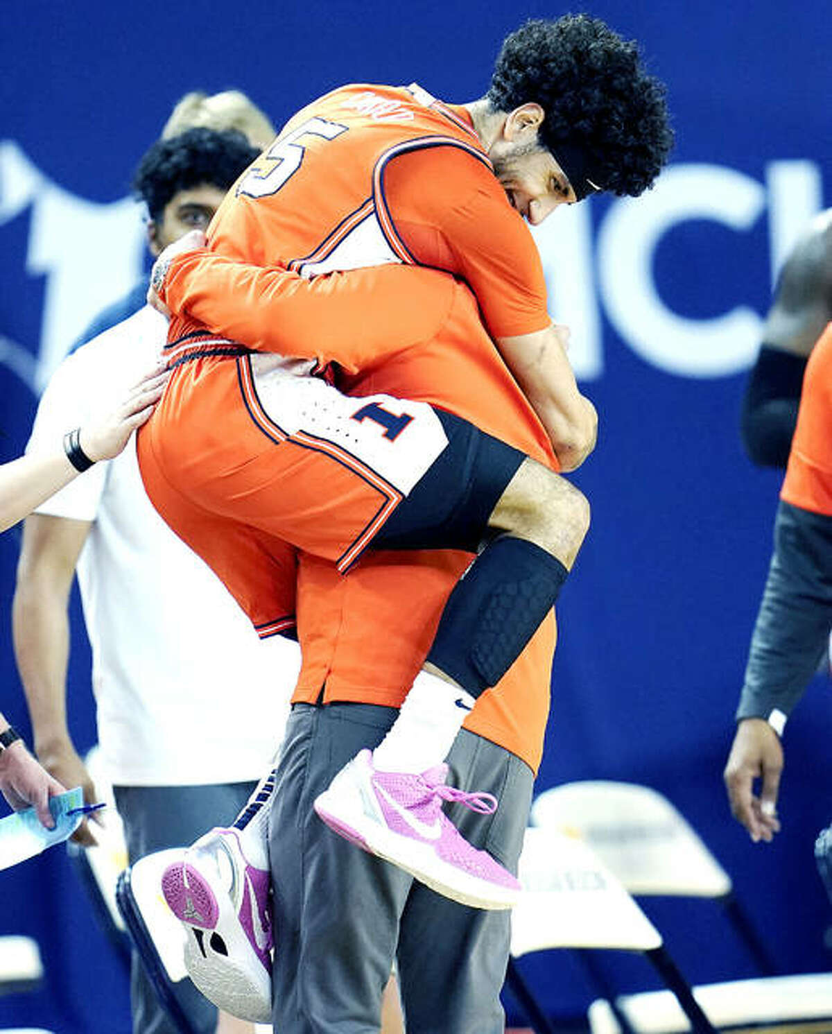 Illinois guard Andre Curbelo (5) jumps into the arms of head coach Brad Underwood in the closing moments of a 76-53 Illini victory in Ann Arbor, Mich.