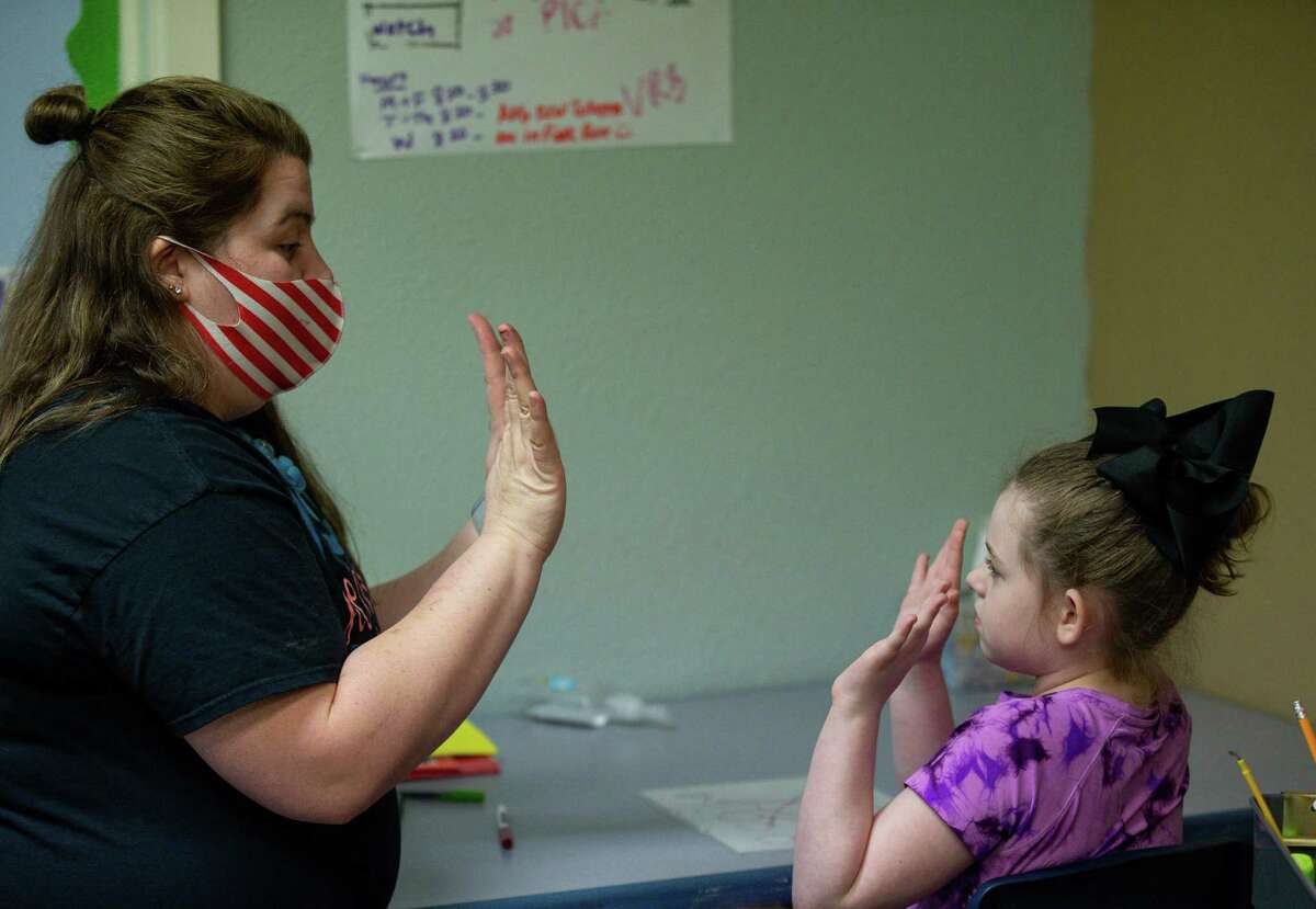 The Grove ABA board-certified behavior analyst Brittney Lewis, left, high-fives AnaMaria Gorman at Texas Autism Academy in The Woodlands. Texas Autism Academy incorporates behavioral therapy in the curriculum for its 22 students, ages 4-14.