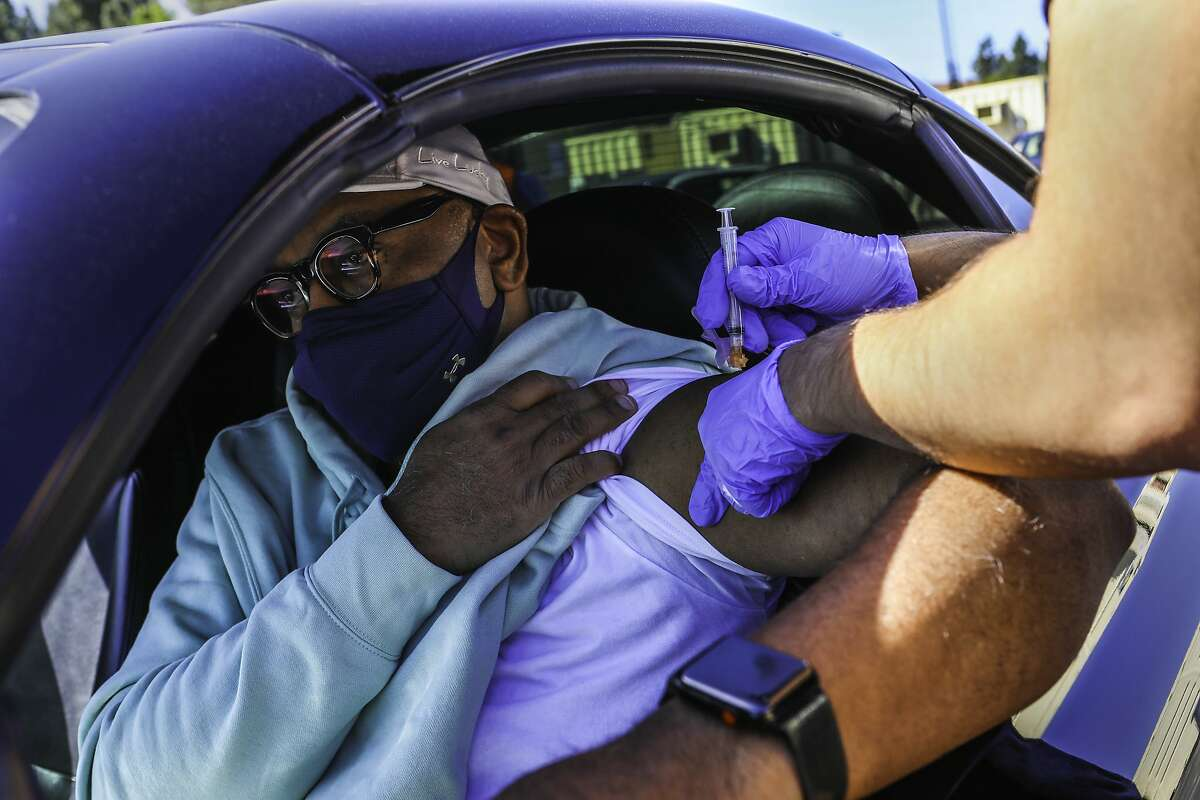 """Derrick Sheppard, 53, of Danville, receives the Johnson and Johnson vaccine at the new drive-through COVID-19 vaccination site at Hurricane Harbor Concord on Wednesday, March 31, 2021, in Concord, Calif. """"I want to protect, of course, myself and my family, but also my community and some of the older folks in my family as well. I'm very mindful of that,"""" Sheppard said."""