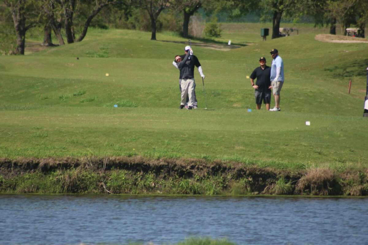 A foursome attempts to hit over this water hazard during Monday's tournament.