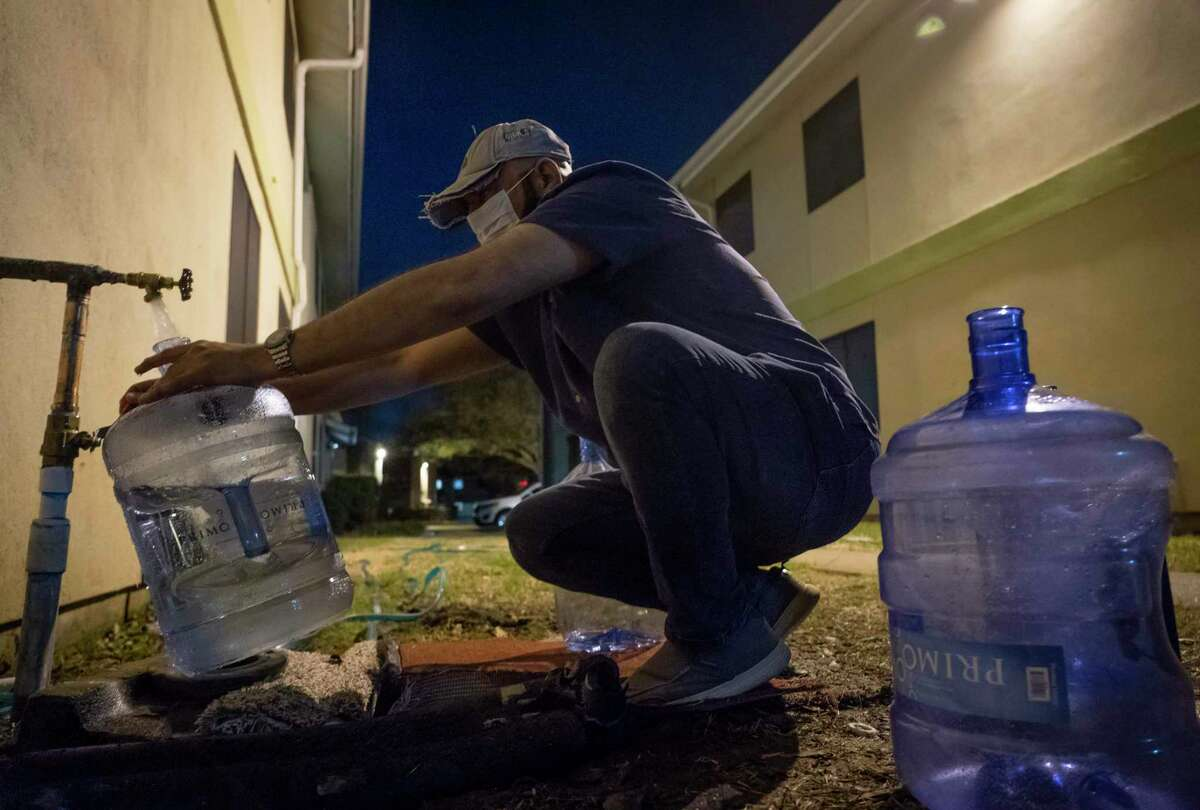 Haitham Nash fills up water bottles from a spigot outside a building in Houston his apartment complex on Sunday, March 7, 2021. Nash lacked running water for weeks after the February winter storm.