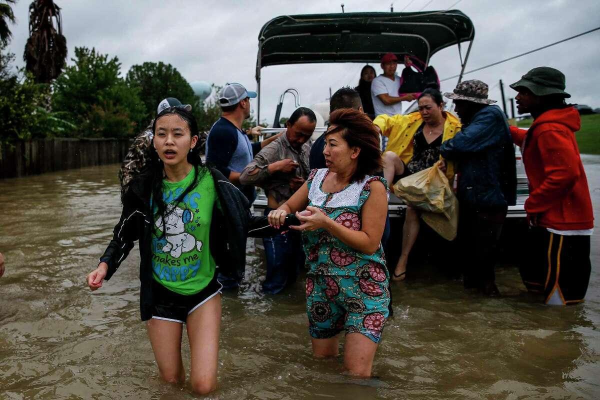 Stephanie Vu, left, holds hands with her mother, Tracy Cao, as they evacuate from the Savannah Estates neighborhood as Addicks Reservoir nears capacity Tuesday, Aug. 29, 2017 in Houston. ( Michael Ciaglo / Houston Chronicle)