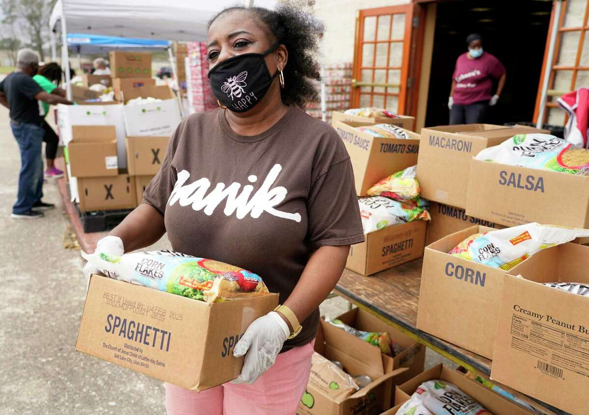Volunteer Veronica McClendon carries a box to a vehicle at the Community of Faith's food pantry program Wednesday, March 10, 2021 in Houston. She is experiencing long term unemployment during the COVID-19 pandemic.