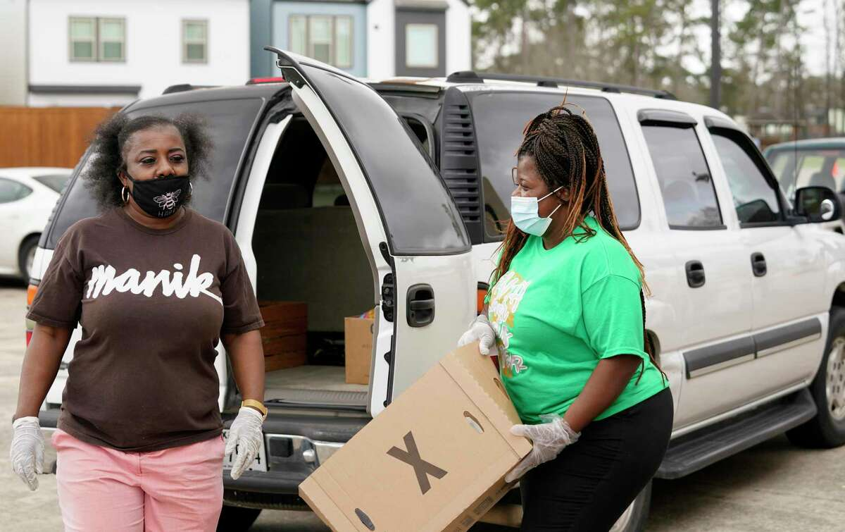 Volunteers Veronica McClendon, left, and Shronda Williams, right, load vehicles at the Community of Faith's food pantry program Wednesday, March 10, 2021 in Houston. Both are experiencing long term unemployment during the COVID-19 pandemic.