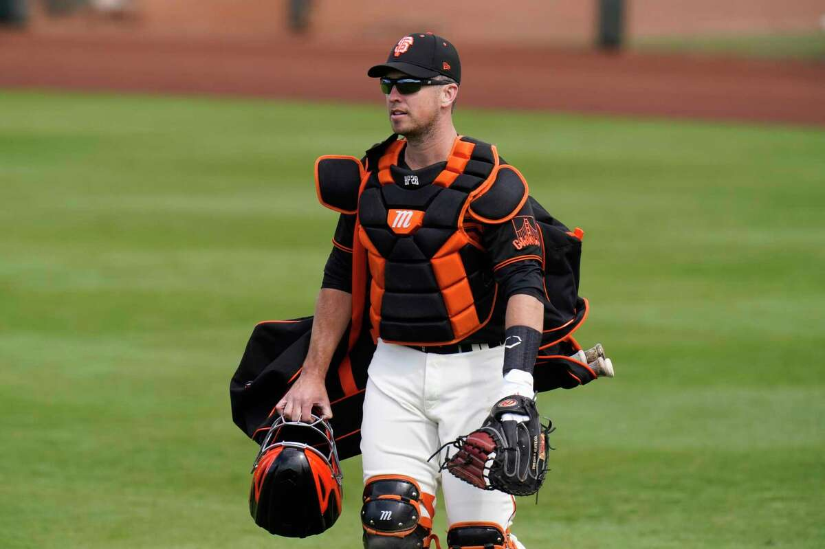 San Francisco Giants catcher Buster Posey walks across the field before the team's spring baseball game against the Los Angeles Angels in Scottsdale, Ariz., Sunday, Feb. 28, 2021. (AP Photo/Jae C. Hong)