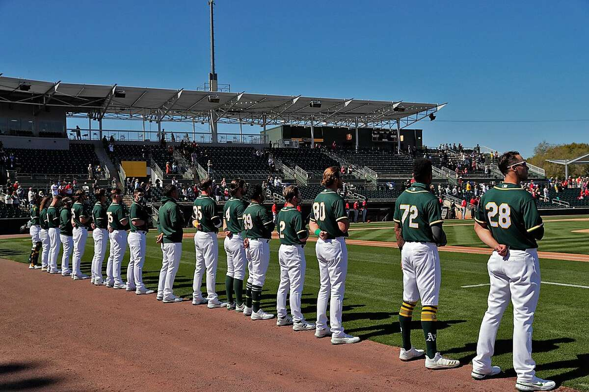The A's stand on the foul line for the national anthem with a nearly empty stadium behind them before their March 1 spring training game against Cincinnati at Hohokam Stadium in Mesa, Ariz.