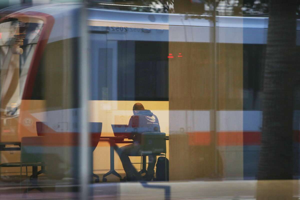 A person is seen working at a table at 1515 Third Street as a street car passing on Third Street is reflected on the exterior of the building at 1515 Third Street on Monday, March 29, 2021 in San Francisco, Calif.