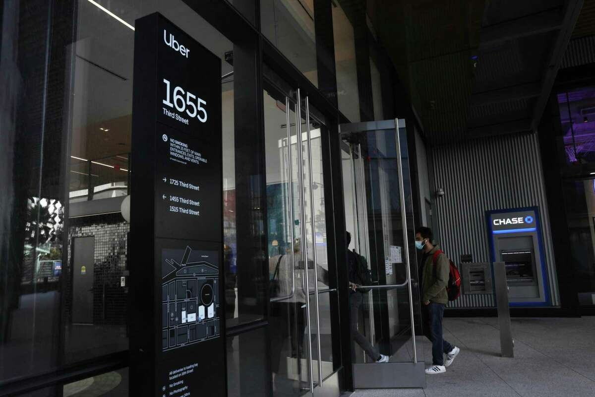People are seen entering the Uber building at 1655 Third Street on Monday, March 29, 2021 in San Francisco, Calif.