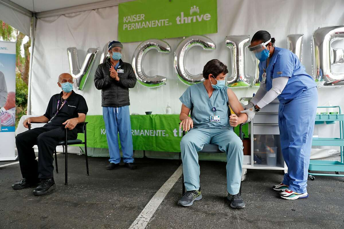 Kaiser San Rafael Medical Center nurse Doug Clark receives the coronavirus vaccine from nurse Meka Parks after employee Charles Hill was vaccinated by nurse Itamar Bikszer in San Rafael, Calif., on Wednesday, December 16, 2020.