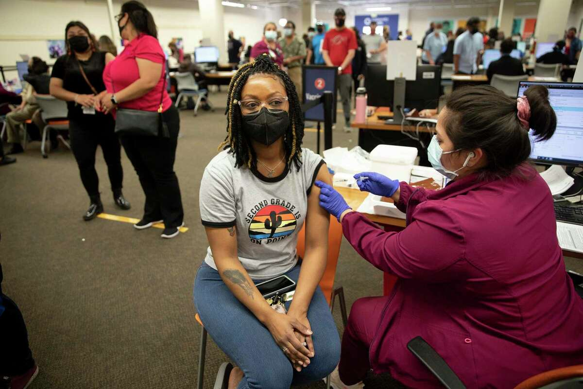 Ilene Bruce, 35, receives her first dose of COVID-19 vaccine at the Wonderland of the Americas mall on the first day all Texas adults became eligible to receive the shots.