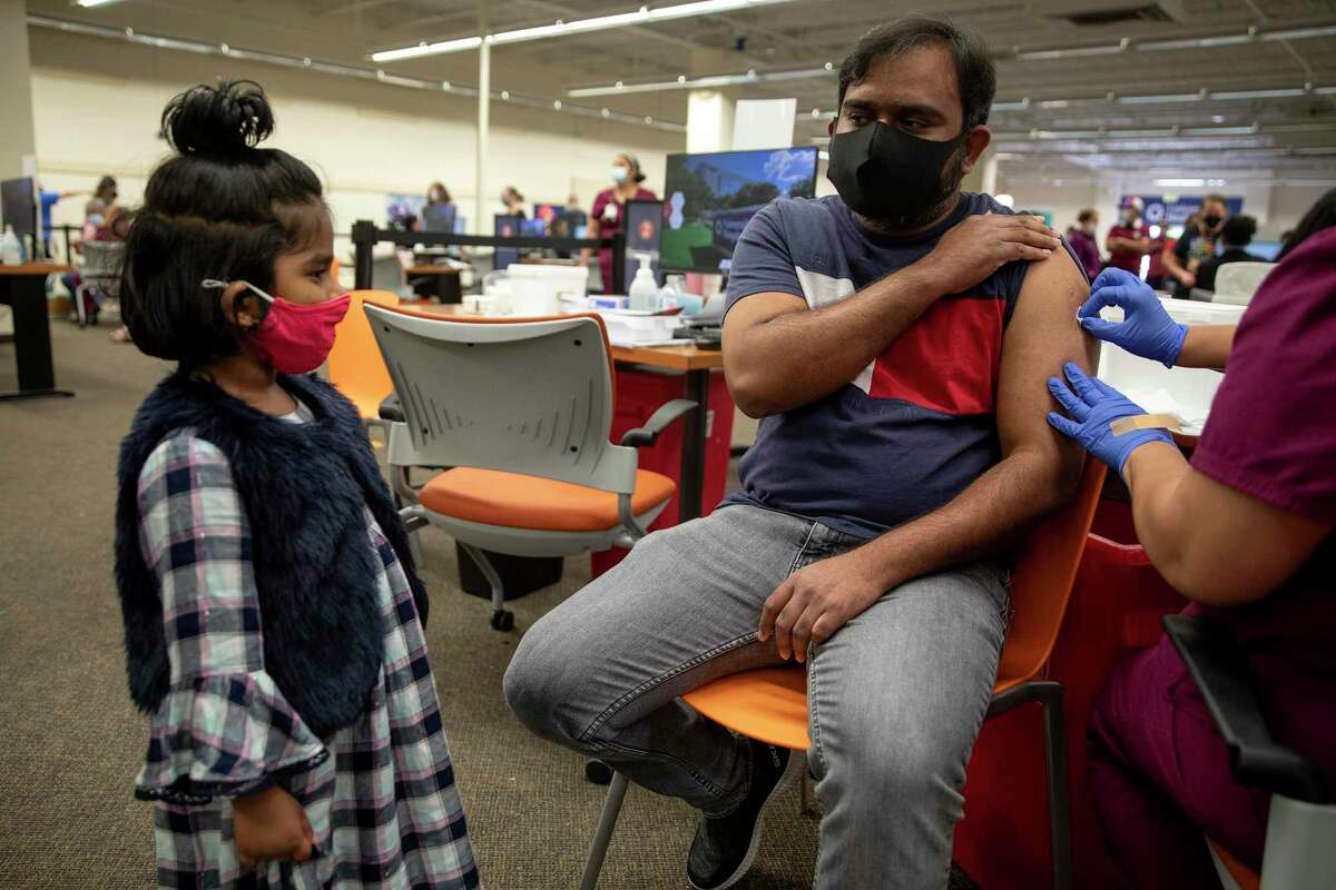 Raj Soundarrajan watches his daughter Ria Senthilraj before he gets a COVID-19 shot at the Wonderland of the Americas mall.