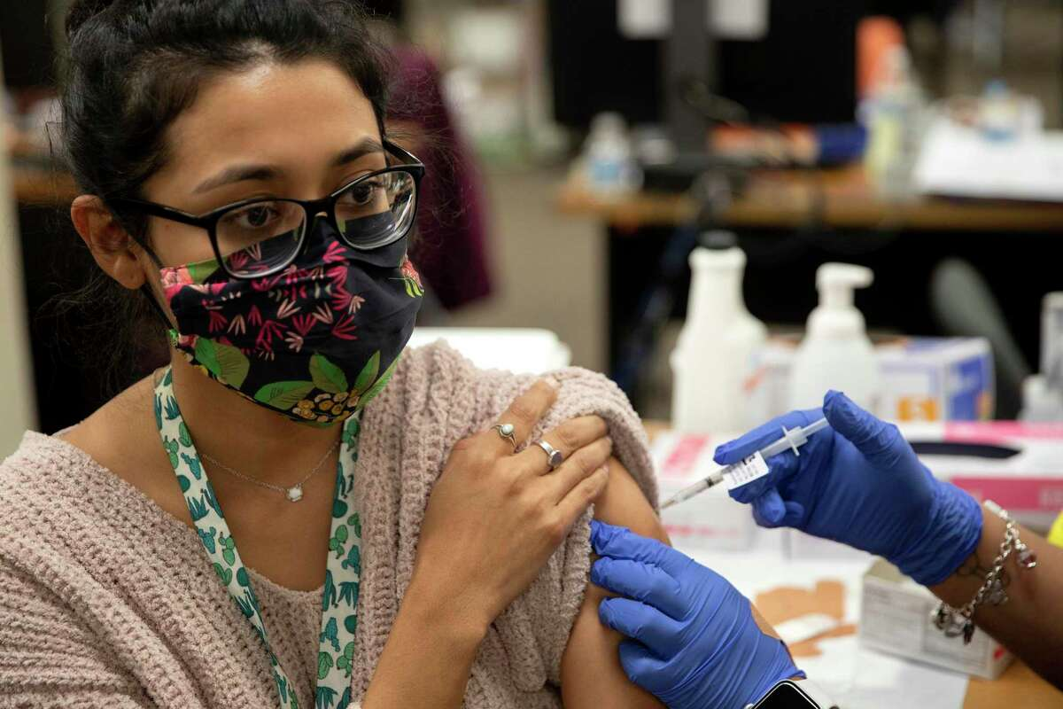 Adriana Carolina Espinoza, 23, receives her first dose of the COVID-19 vaccine on the first day appointments were open to anyone over the age of 16.