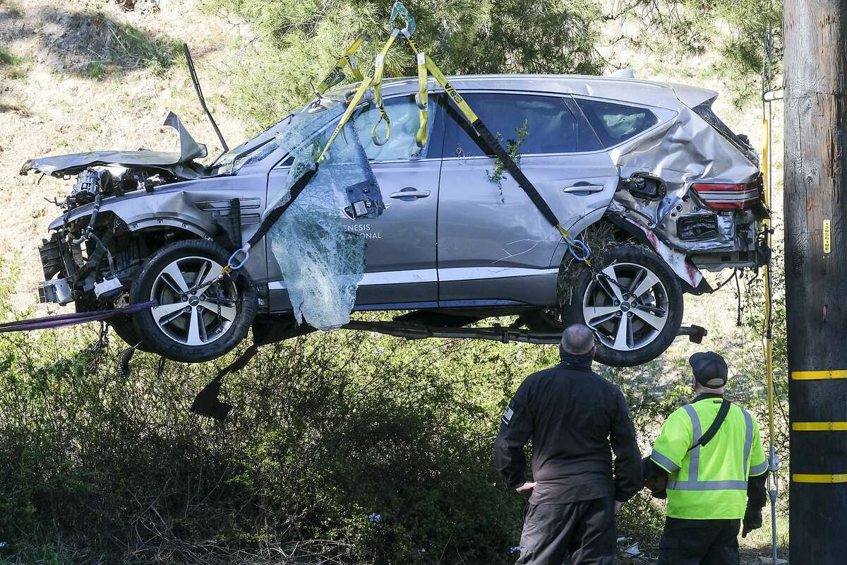FILE - In this Feb. 23, 2021, file photo a crane is used to lift a vehicle following a rollover accident involving golfer Tiger Woods, in the Rancho Palos Verdes suburb of Los Angeles. The Los Angeles County sheriff says detectives have determined what caused Woods to crash his SUV last month in Southern California but would not release details on Wednesday, March 31, 2021, citing privacy concerns for the golf star. (AP Photo/Ringo H.W. Chiu, File)