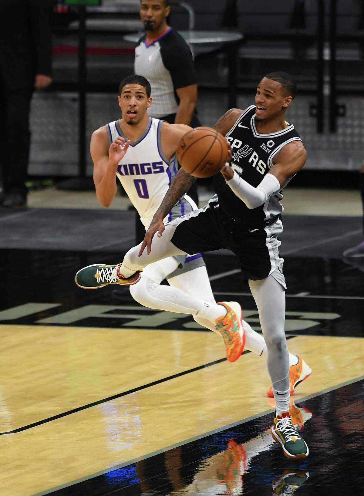 DeJounte Murray of the San Antonio Spurs saves the ball from going out of bounds as Tyrese Haliburton of the Sacramento Kings watches during NBA action in the AT&T Center on Wednesday, March 31, 2021.