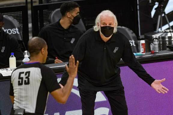 San Antonio Spurs coach Gregg Popovich questions a call as basketball official John Butler runs by during NBA action against Sacramento in the AT&T Center on Wednesday, March 31, 2021.