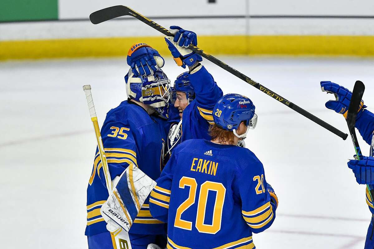 Buffalo Sabres goalie Linus Ullmark (35) celebrates with defenseman Brandon Montour (62) after an NHL hockey game against the Philadelphia Flyers in Buffalo, N.Y., Wednesday, March. 31, 2021. Montour scored two short-handed goals in 37 seconds as Buffalo beat Philadelphia 6-1 to break an 18-game winless streak. (AP Photo/Adrian Kraus)