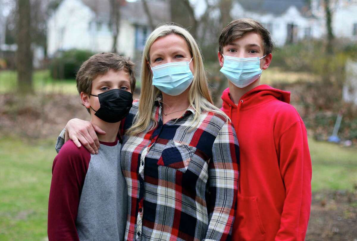 Kristina Gregory, center, poses with her sons Nathan, 12, left, and Peter, 15, at their home in Darien, Conn., on Wednesday March 31, 2021. Gregory is supportive of getting her sons vaccinated when they are eligible after having a tough journey with COVID a year ago that continues to have lingering effects.