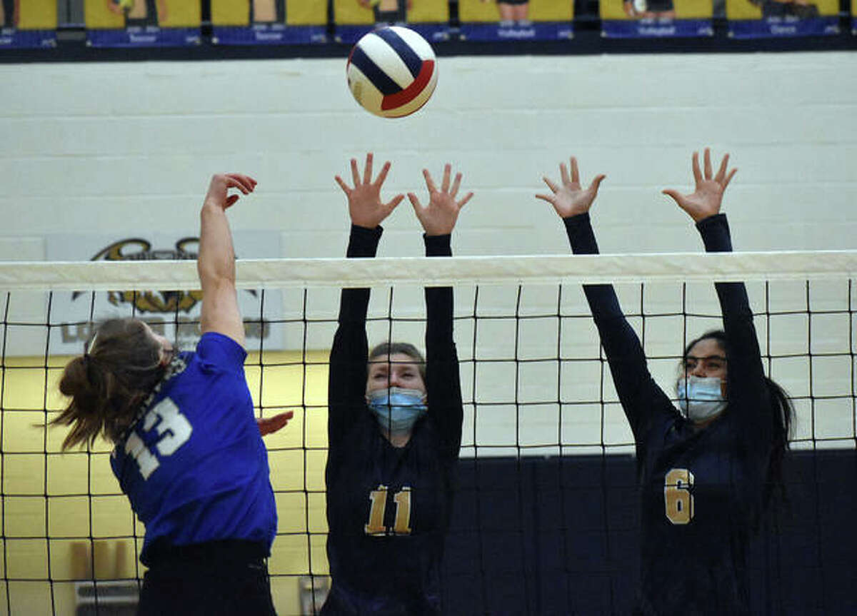 Father McGivney's Emma Bukovac, center, and Haydee Rios, right, attempt to block an attack from a Marquette Catholic hitter.