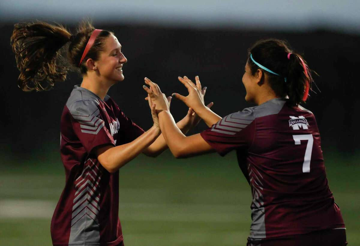 Magnolia's Sara Giannotti, left, celebrates with Gaby Palomino after scoring her second of three goals during the second period of a bi-district high school soccer match, Friday, March 26, 2021, in Waller.