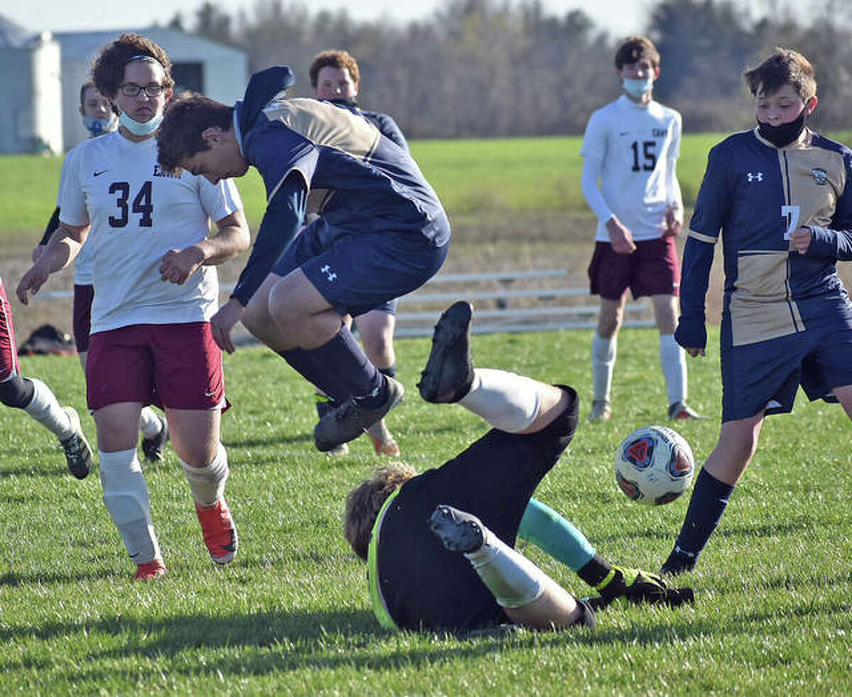 Father McGivney's Sam Chouinard leaps over the EA-WR keeper during the second half on Wednesday in Glen Carbon. Father McGivney's Drew Villhard is also pictured.