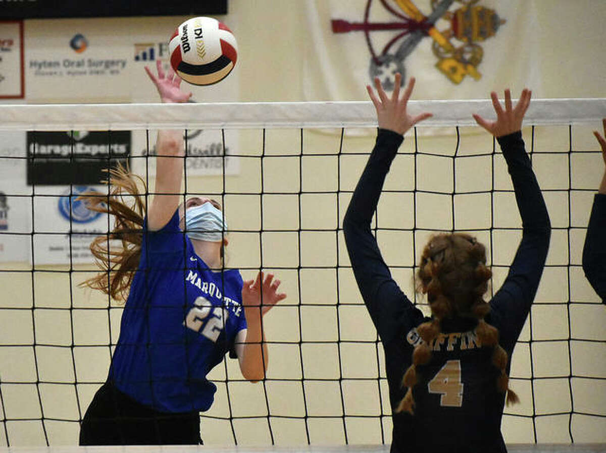 Marquette Catholic's Olivia Ellebracht (left) goes up for an attack with Father McGivney's Anna McKee attempting to block it in a girls volleyball match Wednesday night in Glen Carbon.