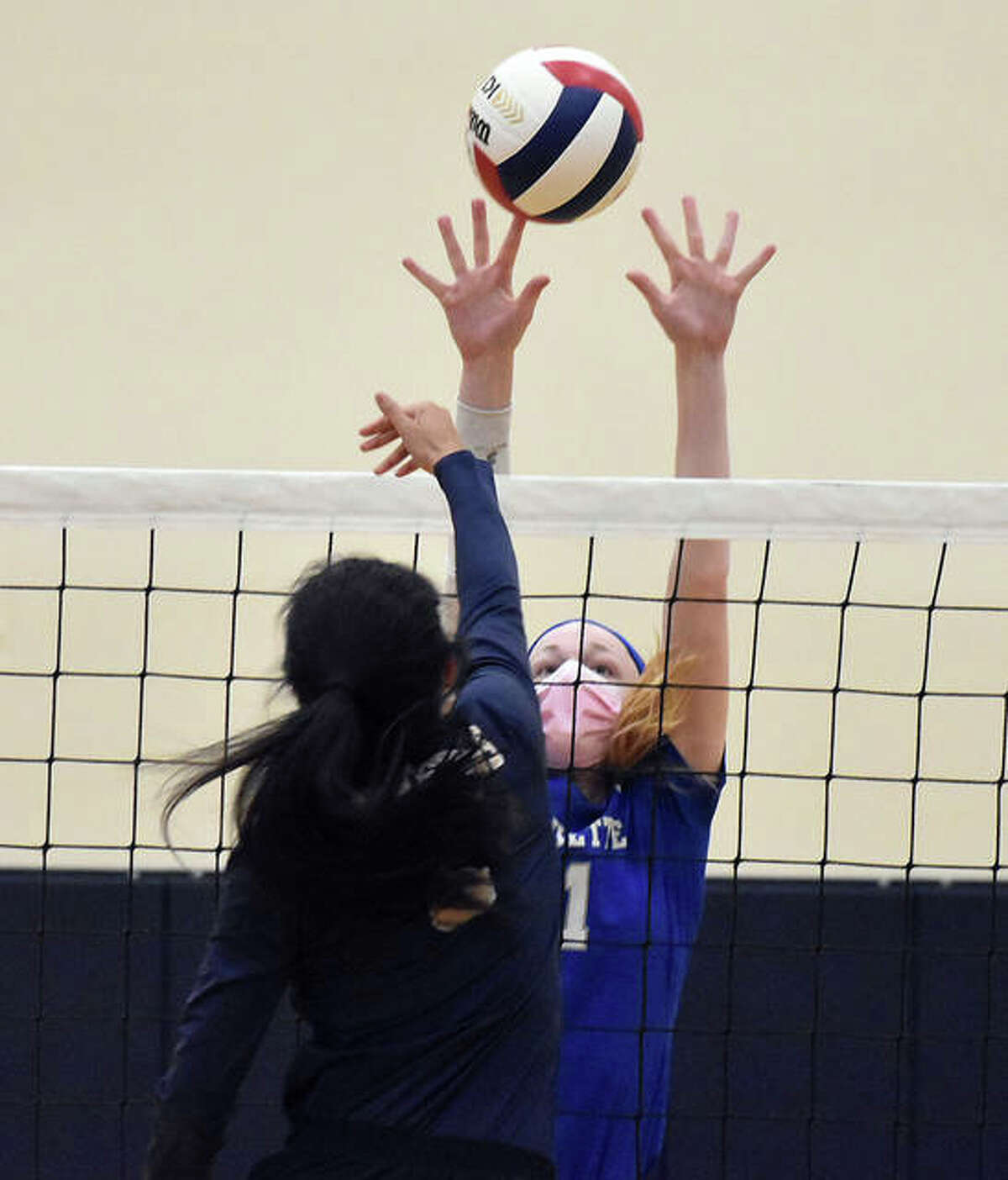Marquette Catholic's Emma Menke tries to block a hit from Father McGivney's Haydee Rios during the second game.